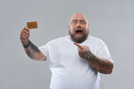 Waist up of fat bearded man expressing excitement while standing isolated on the grey background and pointing to the gold card in his hand