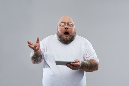 Surprised fat bearded man standing isolated on the grey background and opening his mouth while holding modern smartphone and gesturing