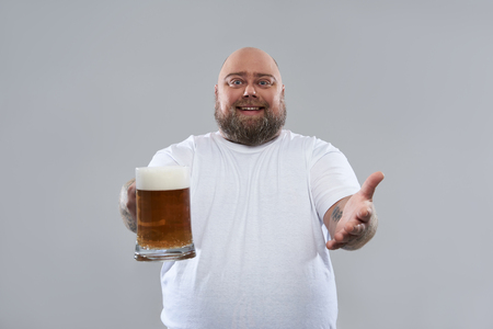 Isolated on the grey background photo of positive bearded man holding a big glass of beer and smiling 免版税图像