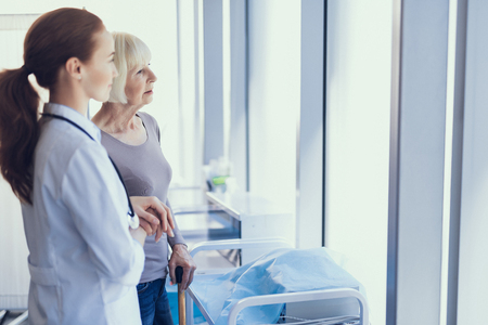 Focus on tranquil aged lady standing and using crutch in medical office. Attentive female physician is supporting her by hand while they are looking forward