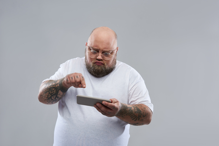 Waist up isolated on the grey background image of concentrated Caucasian bearded man in white T-shirt standing alone and frowning while using his smartphone