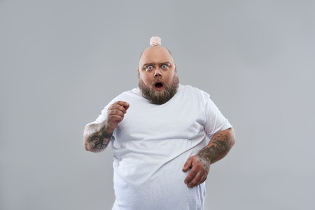 Waist up of fat surprised man standing isolated on the grey background and opening his mouth while having marshmallow souffle on his bold head