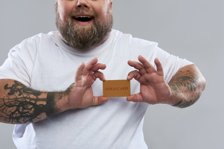 Close up of happy bearded man with tattooed arms standing alone and smiling while holding a gold card in front of his heart