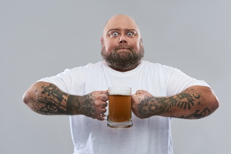 Fat bearded confident man standing in white T-shirt and opening his eyes wide while holding a big glass of beer Stock fotó