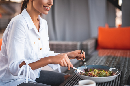 Close up of the cafe table with a bowl of salad on it and smiling young woman using knife and fork while eating