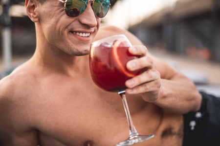 Happy relaxed shirtless man in sunglasses smiling and revealing his teeth while holding a glass of cold cocktail Stock Photo