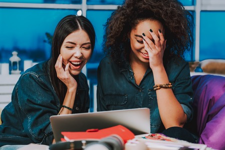 Oh my god, what is picture. Laughing asian and african female having fun while looking at screen of computer