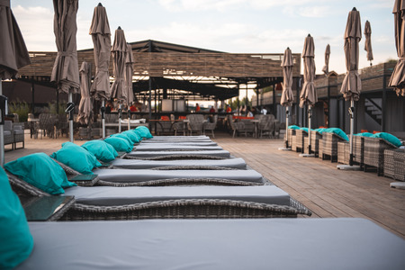 View on the wooden terrace with comfortable lounge sun chairs and big beach umbrellas. Cafe on the background