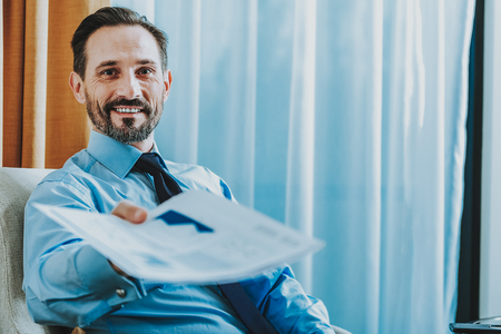 Everything is ready. Confident businessman in shirt and tie smiling to the camera and giving the documents. Copy space on the right side Stock Photo