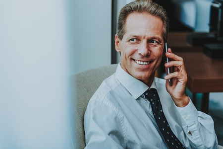 Happy mature businessman in shirt and tie sitting next to the window and smiling while talking on the phone and looking into the distance 版權商用圖片 - 117406945