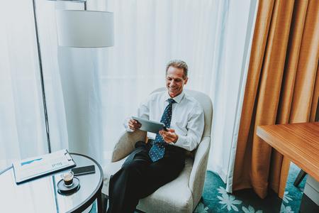 Hombre de negocios con tableta. Feliz empresario entusiasta que parece contento mientras está sentado en el sillón con una mesa de café frente a él y usando una tableta moderna