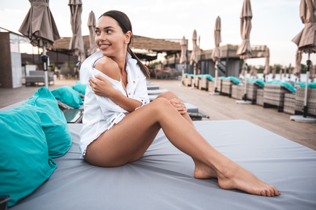 Full length of young woman wearing swimsuit and blouse while sitting on the lounge sun chair on the beach and smiling while turning back Stock Photo