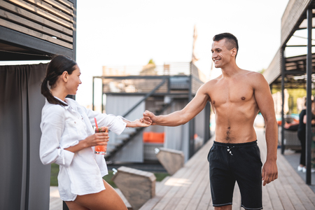 Playful mood. Positive long haired lady with cocktail pulling the hand of her smiling shirtless boyfriend while being outdoors with him