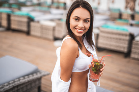 Dark haired woman in white swimsuit sitting alone with cocktail I her hand and revealing her teeth while smiling