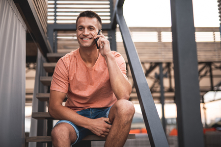 Phone talk outdoors. Positive young man wearing casual T-shirt and shorts and smiling while having a pleasant phone talk Stock Photo