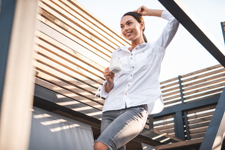 Cheerful dark haired young woman enjoying sunny day and smiling while standing with a cup of coffee on the stairs