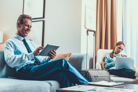 Middle aged businessman sitting with his tablet on the sofa and having suitcase by his side while calm woman using her device on the armchair