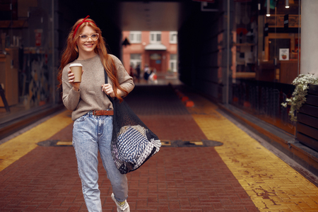 Portrait of beautiful red-haired lady with laundry holding cup of coffee while standing on the street. She looking away and smiling