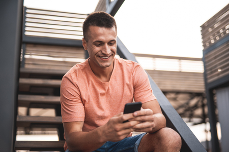 Waist up of cheerful young man in casual clothes smiling while sitting on the stairs and looking at the screen of his modern smartphone