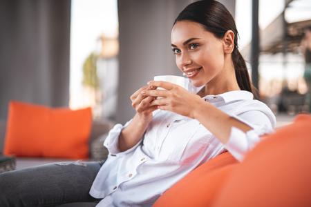 Bastante joven sentada sola y poniendo un codo sobre la almohada suave mientras sostiene una taza de café y mira a lo lejos