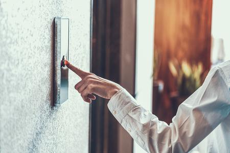 Gros plan sur une femme en chemise blanche debout et en poussant le bouton de l'ascenseur avec son index