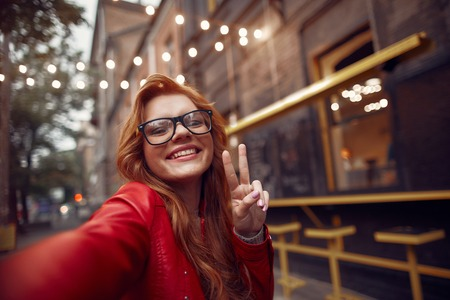 Close up portrait of charming young lady in glasses showing victory gesture and looking at camera with happy smile
