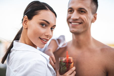Attractive young dark haired lady looking curious and confident while standing with her boyfriend and holding tasty cocktail