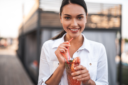 Delicious drink. Waist up of a beautiful dark haired young woman in white blouse standing outdoors with cocktail in her hands and smiling
