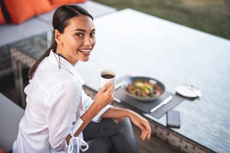 Cheerful dark haired young lady sitting at the cafe table with a cup of coffee and revealing her teeth while smiling