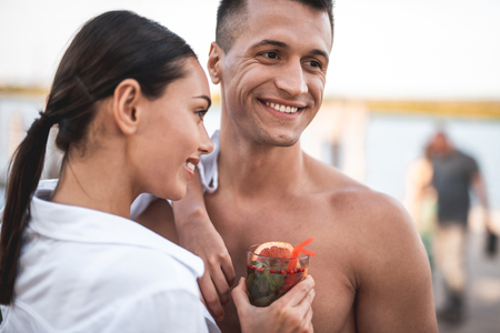 Dark haired young lady standing close to her shirtless handsome boyfriend and smiling while holding a delicious cocktail