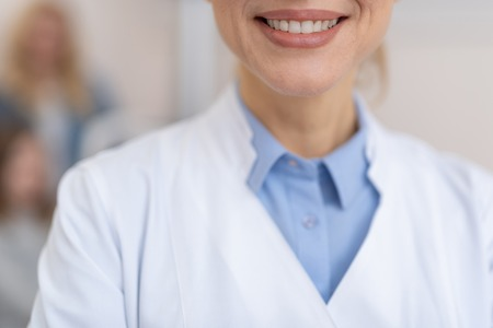 Cropped close up portrait of charming middle-aged woman in white lab coat smiling
