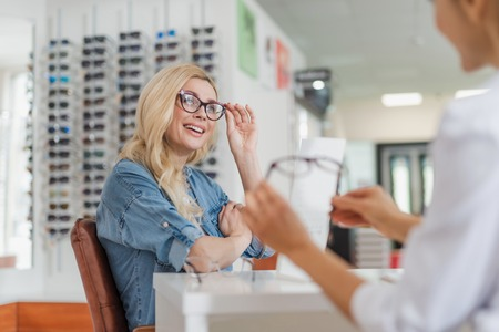 Cheerful nice woman sitting at the table while consulting with a professional ophthalmologist at optical store Foto de archivo