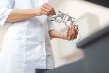 Close up low angle picture of female optometrist preparing ophthalmic testing device for eyesight examination Stockfoto