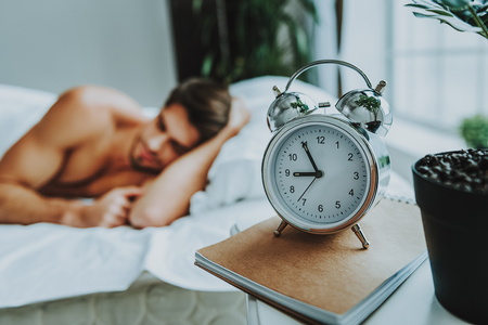 It is time to wake up. Close up selective focus on alarm clock staying on table near bed where young attractive man sleeping in the morning Banco de Imagens