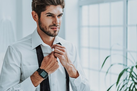 Ready for going on meeting. Close up portrait of confident business man buttoning his shirt while standing before mirror at home