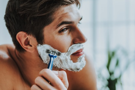Preparing for new coming day. Close up portrait of smiling handsome man using razor to shave his beard while standing before mirror