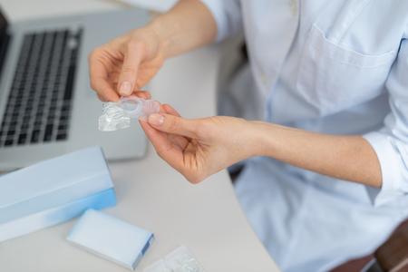 Cerca de las manos del óptico femenino demostrando lentes de contacto. Señora sentada a la mesa con ordenador portátil y caja de embalaje azul