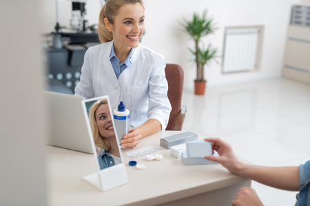 Blond lady having consultation with highly qualified optician. Doctor sitting at the table with laptop and holding bottle of lens solution