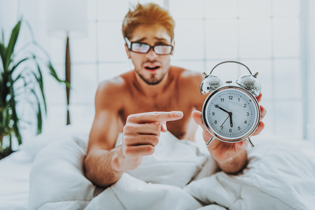 Oversleeping concept. Selective focus of alarm clock face in hands of upset young man pointing to missing time of waking up