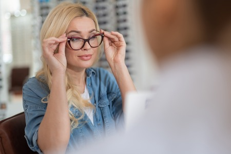 Delighted beautiful woman wearing glasses while waiting for recommendation of the ophthalmologist