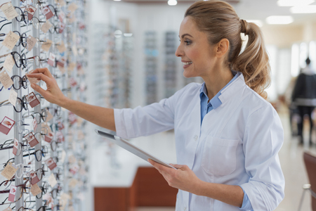 Cheerful professional ophthalmologist working at the optical store while enjoying her daily requirements