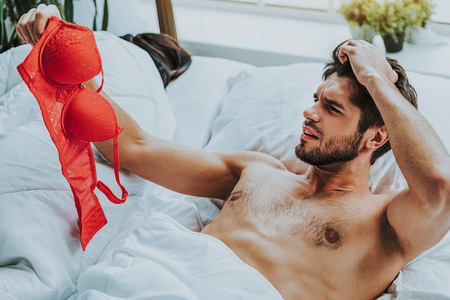 I dont remember anything. Waist up portrait of attractive man looking very shocked after waking up and finding sexy female red bra in his bed