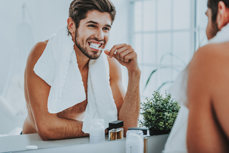 Taking care of dental health. Waist up portrait of sexy muscular man brushing his teeth after shower while standing before mirror at home