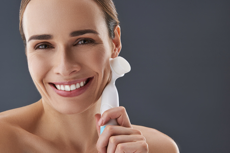 Close up cropped photo of smiling naked shoulders lady standing isolated on gray background with peeling massage brush in hand Banque d'images - 117424824