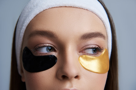 Say no to wrinkles and dark circles. Close up of girl with multicolored masks under lower eyelids looking away Stock Photo