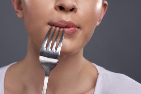 Cerca de la niña con el utensilio para comer sintiendo hambre. Aislado sobre fondo gris