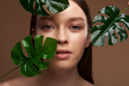 Close up portrait of beautiful young woman with green tropical leaves looking at camera with slightly open mouth