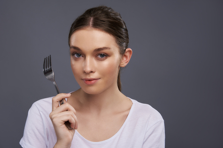 Portrait of beautiful girl with eating utensil looking at camera and smiling slightly. Isolated on blue gray background