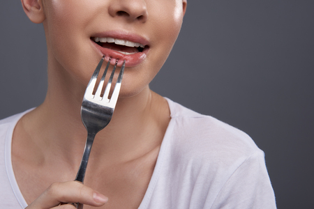 I am so hungry. Close up of girl with eating utensil keeping mouth open. Isolated on blue gray background Stock fotó