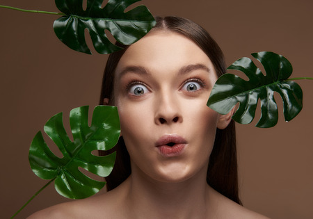 Close up portrait of young woman with tropical leaves pouting lips and doing hilarious grimace. Isolated on brown background